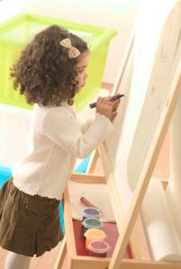 cute little girl continuing to paint